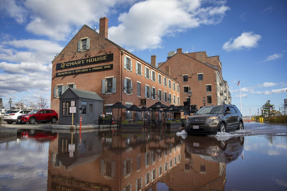 A car drives through flood water by the Chart House on Boston's Long Wharf during a November king tide. (Robin Lubbock/WBUR)