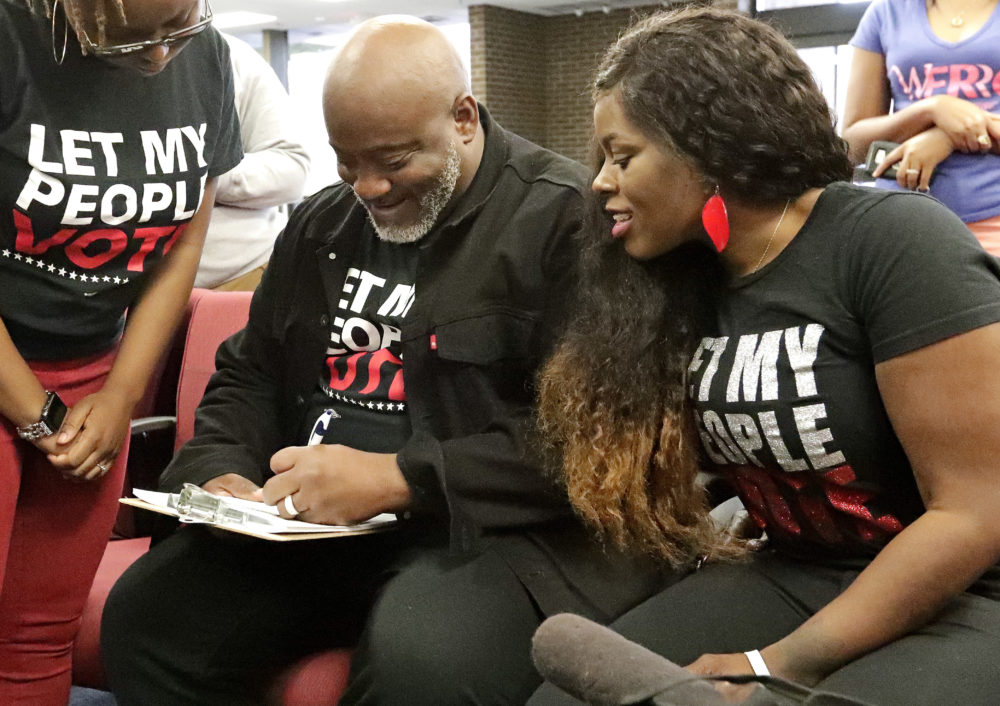Desmond Meade (left), president of the Florida Rights Restoration Coalition, fills out a voter registration form as his wife Sheena Meade looks on at the Supervisor of Elections office in Orlando, Florida. (John Raoux, File/AP)