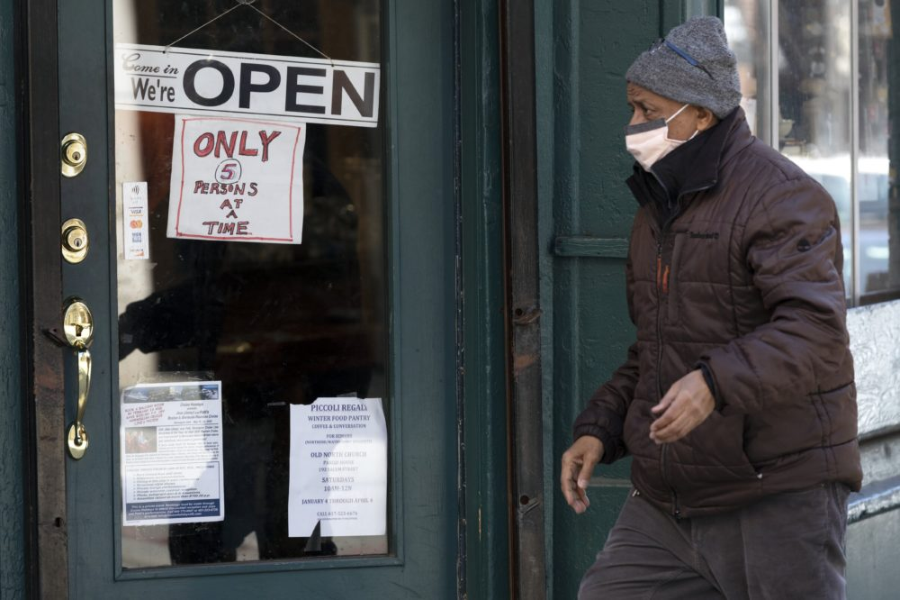 A man walks past a shop, open for business in the North End neighborhood of Boston, but only allowing five customers at a time, March 21, 2020. (Michael Dwyer/AP)