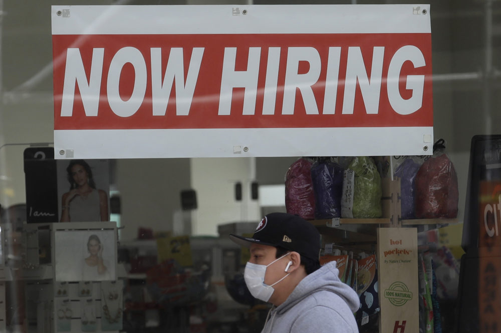 This May 7, 2020, file photo shows a man wearing a mask while walking under a Now Hiring sign at a CVS Pharmacy during the coronavirus outbreak in San Francisco.(Jeff Chiu/AP File)
