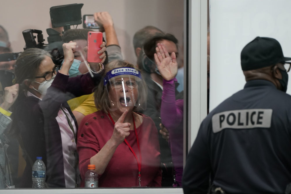 Pro-Trump protesters yell as they look through the windows of the central counting board as police were helping to keep others from entering due to overcrowding on Wednesday, Nov. 4, 2020, in Detroit. (Carlos Osorio/AP)