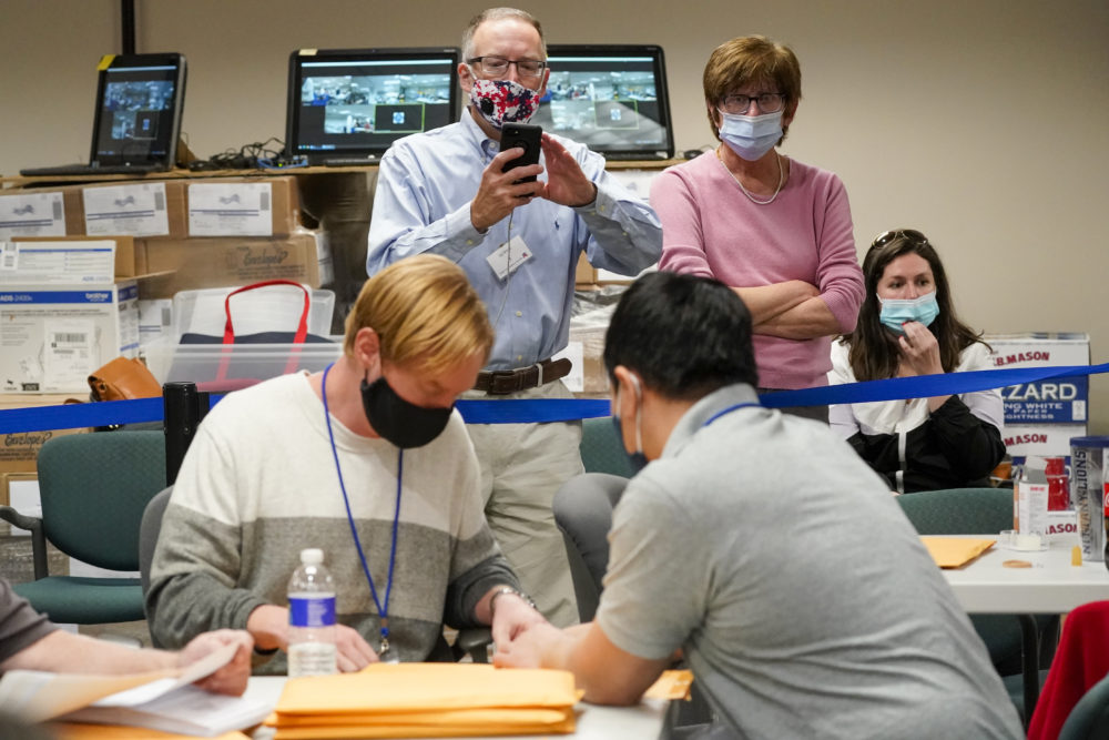 Republican canvas observer Ed White, and Democratic canvas observer Janne Kelhart, watch as Lehigh County workers count ballots as vote counting in the general election on Friday, Nov. 6, 2020, in Allentown, Pennsylvania. (Mary Altaffer/AP)