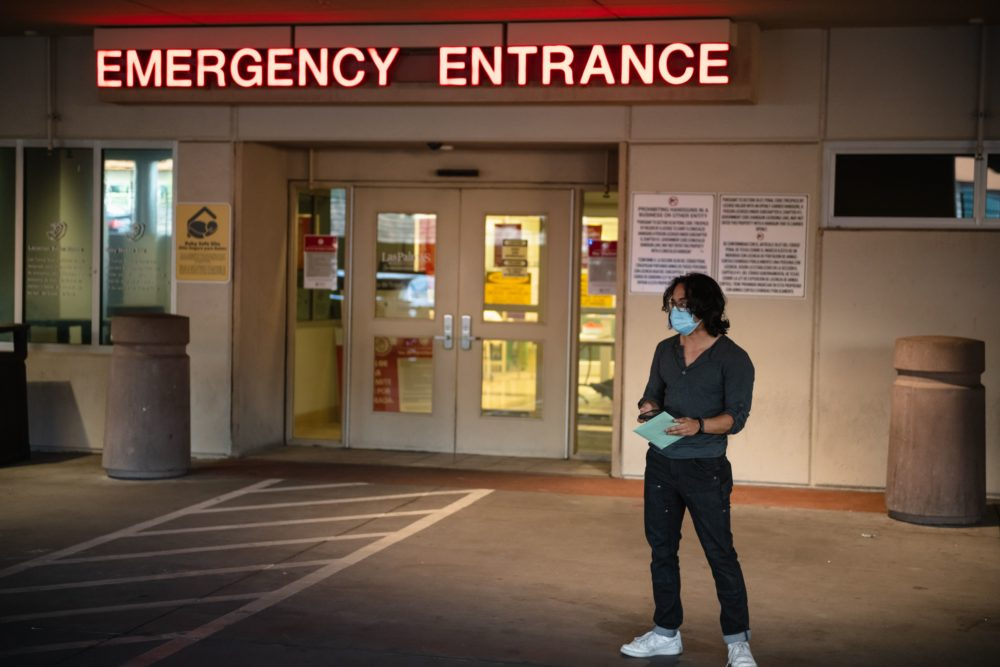Adri Perez, with Common Cause 866ourvote, waits for a nurse to hand deliver an emergency ballot to a person hospitalized with COVID-19 at Las Palmas Medical Center. (Justin Hamel/AFP via Getty Images)