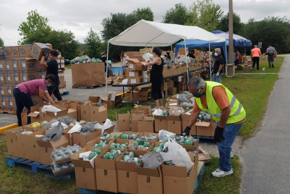 Volunteers prepare food donations from the Second Harvest Food Bank of Central Florida for distribution to needy families at a drive thru event at the New Jerusalem Church in Kissimmee, Florida. (Paul Hennessy/NurPhoto via Getty Images)