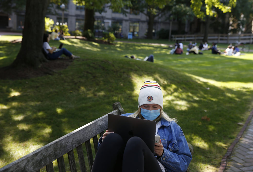 A student works on her laptop outside at Boston University on Sept. 23, 2020. This year, Gov. Charlie Baker is asking colleges to test students before and after any Thanksgiving travel. (Jessica Rinaldi/The Boston Globe via Getty Images)