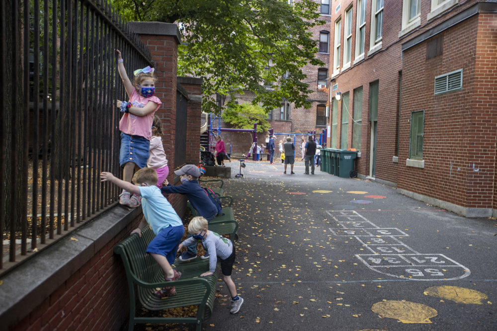 Kids climb the playground fences the Eliot School in the North End in Boston on Oct. 22, 2020. Starting in December, some school students will have access to rapid COVID-19 tests. (Stan Grossfeld/The Boston Globe via Getty Images)
