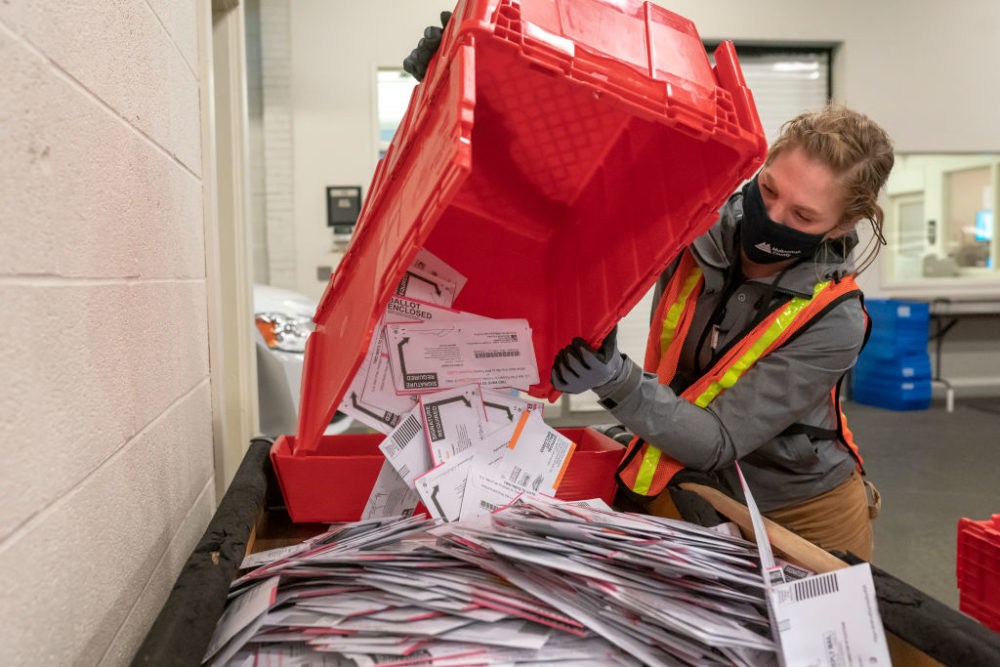 Election worker Sarah Sladek empties a box of submitted ballots at the Multnomah County Elections Office on November 2, 2020 in Portland, Oregon. (Nathan Howard/Getty Images)