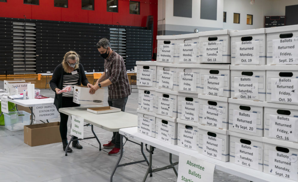 Poll workers Angela and Zach Achten check-in a box of absentee ballots in the gym at Sun Prairie High School on November 3, 2020 in Sun Prairie, Wisconsin. (Andy Manis/Getty Images)