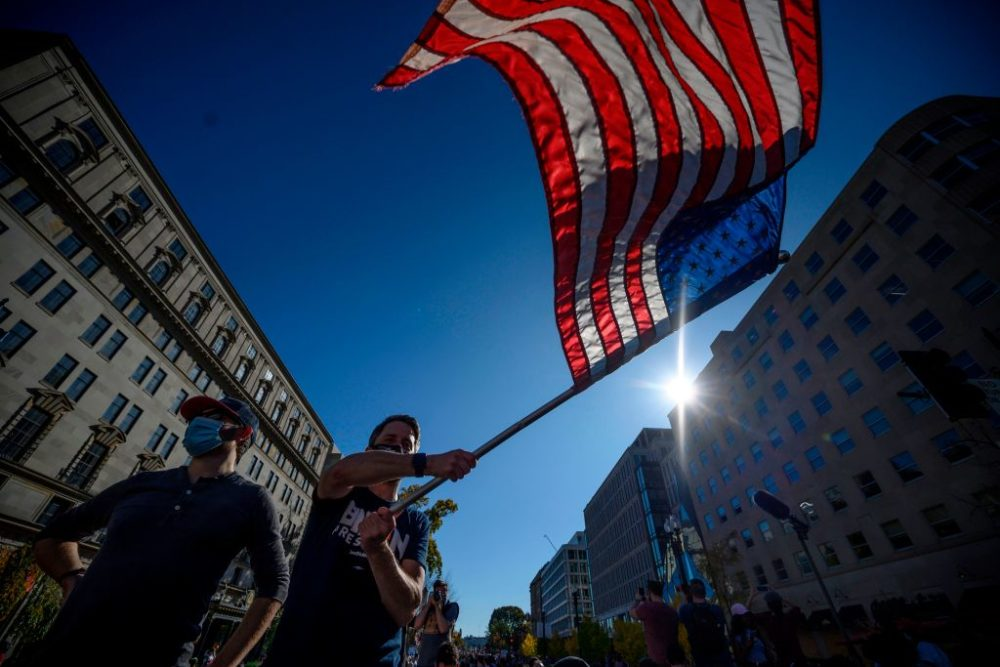 A man waves a U.S. flag as people celebrate in Washington, D.C., after Joe Biden was declared the winner of the 2020 presidential election. (Eric Baradat/AFP/Getty Images)