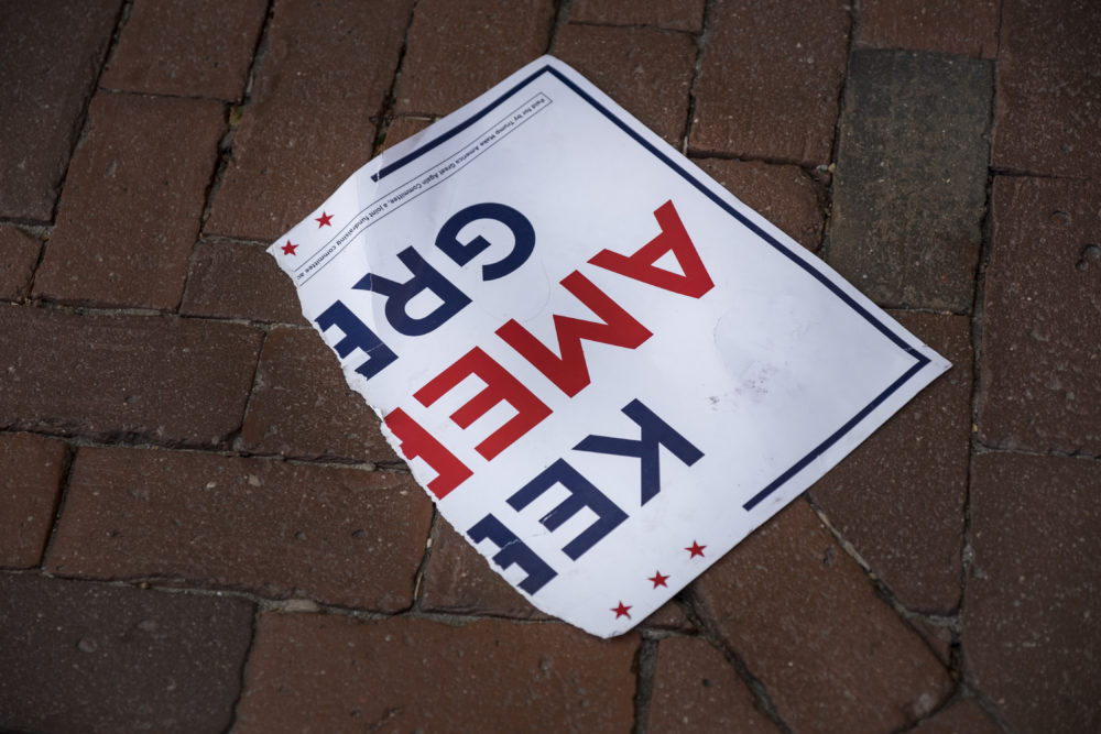 A torn poster on the ground outside the Massachusetts State House in Boston after skirmishes broke out during a demonstration by both Joe Biden and President Trump supporters on the day that the news broke that Biden was declared the winner of the U.S. presidential election Nov. 7, 2020.  (Jodi Hilton/NurPhoto via Getty Images)