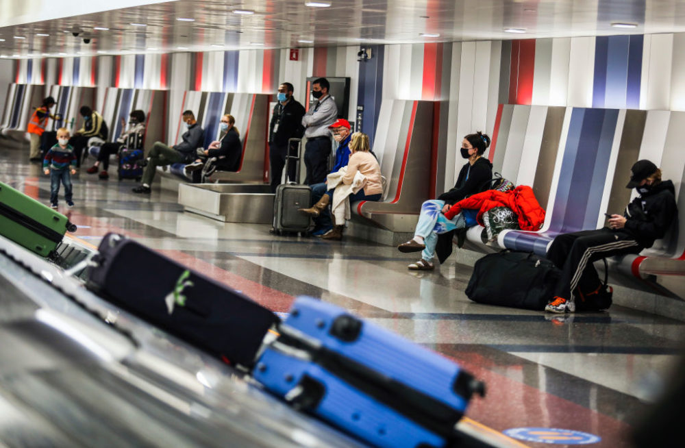 People wait for their baggage at Boston Logan International Airport in Boston on Nov. 25, 2020. The  airport was bustling with travelers on the Eve of Thanksgiving, despite people being encouraged to stay home. (Erin Clark/The Boston Globe via Getty Images)