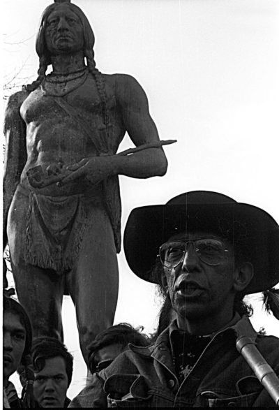 Wamsutta Frank James by statue of Massasoit, in Plymouth, MA on the National Day of Mourning in the 1970s. (Courtesy of guest)