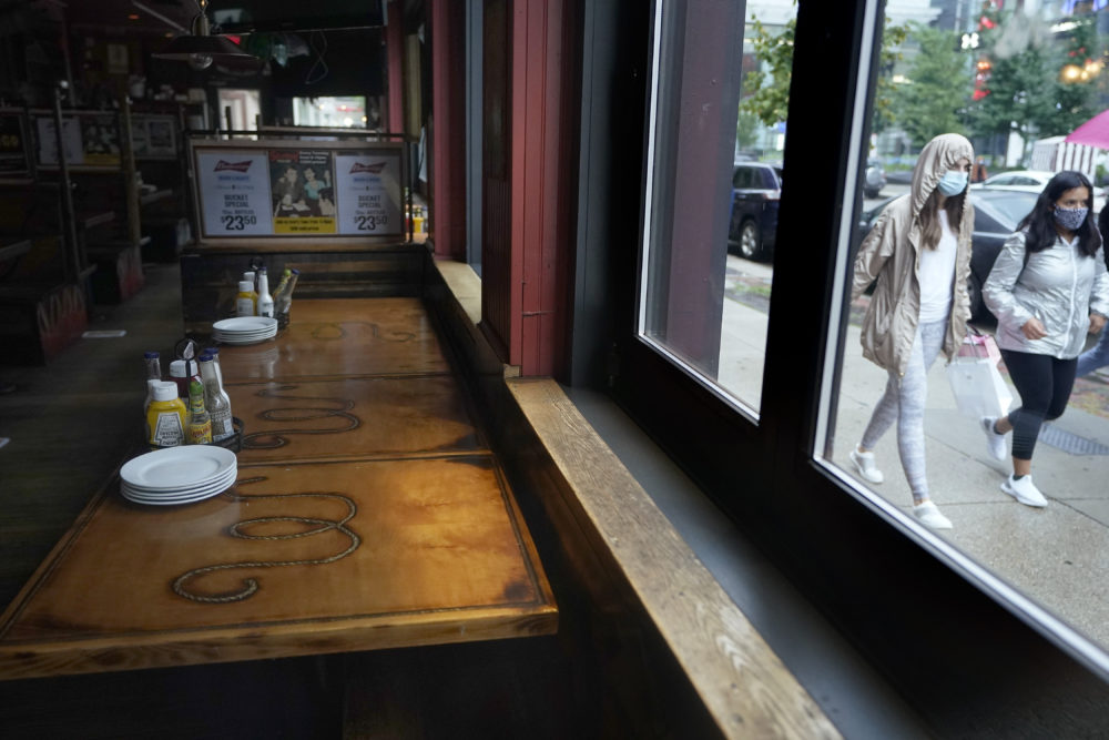 Passersby walk past an empty restaurant in September in Boston. (Steven Senne/AP)