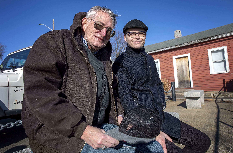 Frank Shaw and Jeremiah MacKinnon enjoy the sunshine on a stone bench overlooking Salem Harbor. (Robin Lubbock/WBUR)