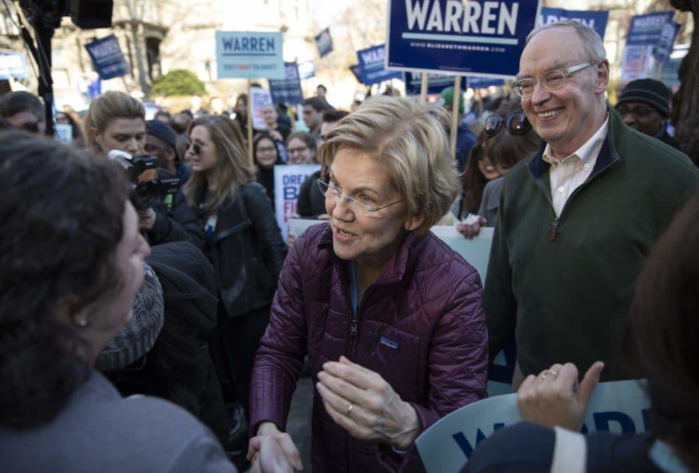 Sen. Elizabeth Warren and her husband Bruce Mann greet supporters on their way to vote in Cambridge, Mass.. (Robin Lubbock/WBUR)
