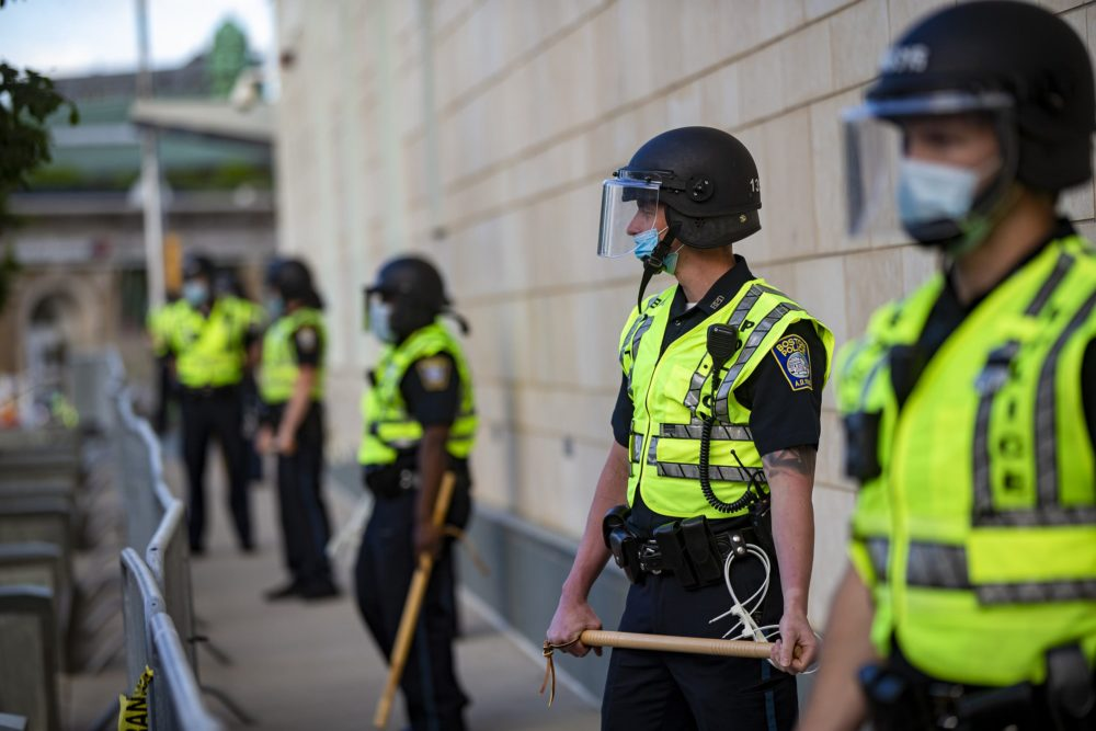Boston police officers with batons lined up outside the District B-2 station in Roxbury before a protest on May 31. (Jesse Costa/WBUR)
