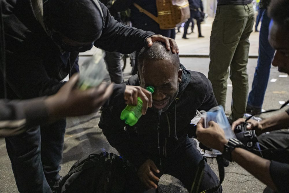 A protester has saline administered to him after he was pepper sprayed by Boston police on School Street after the Black Lives Matter rally at the Massachusetts State House on May 31. (Jesse Costa/WBUR)