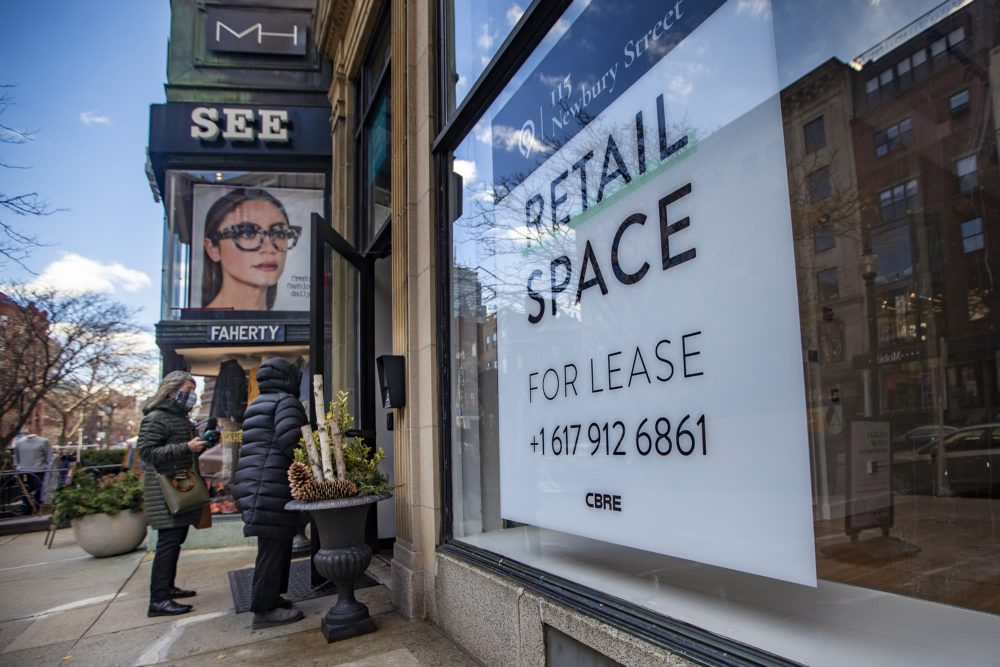 Two shoppers walk into a store next to a vacant retail spot for lease on Newbury Street. (Jesse Costa/WBUR)