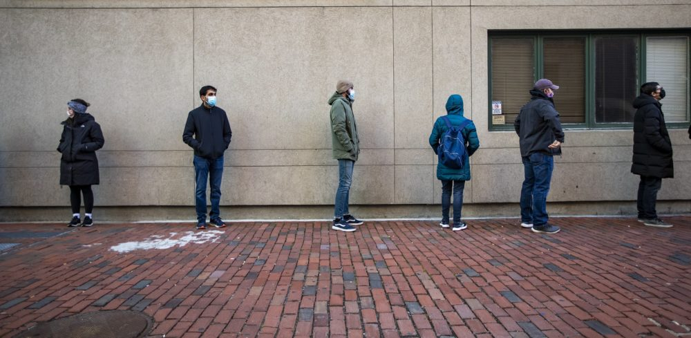 People stand in line and wait to be tested outside of the Tufts coronavirus testing center on Tremont Street. (Jesse Costa/WBUR)