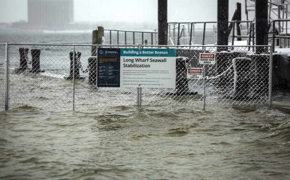 """The fence around a """"Building A Better Boston"""" project gets its feet wet as high tide during the snow storm floods across Long Wharf. (Robin Lubbock/WBUR)"""