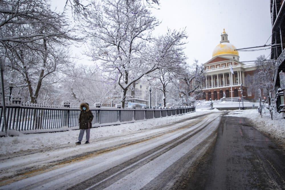 A woman walks down Park Street during the snow storm. (Jesse Costa/WBUR)