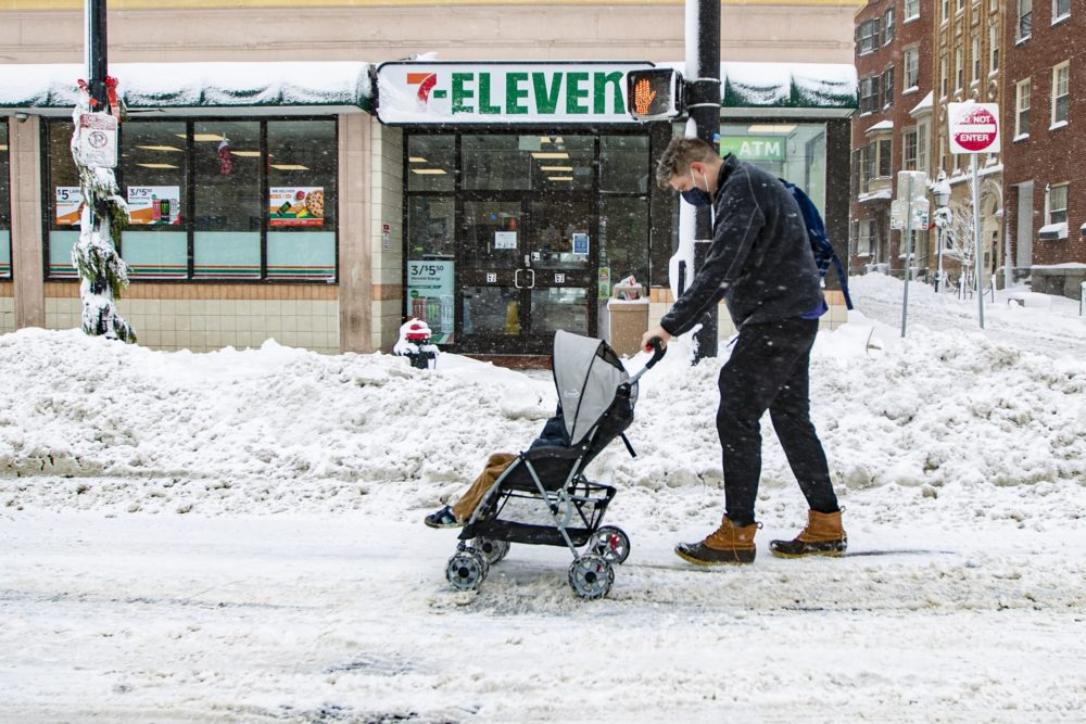 A man pushes a baby in a stroller down Cambridge Street. (Jesse Costa/WBUR)