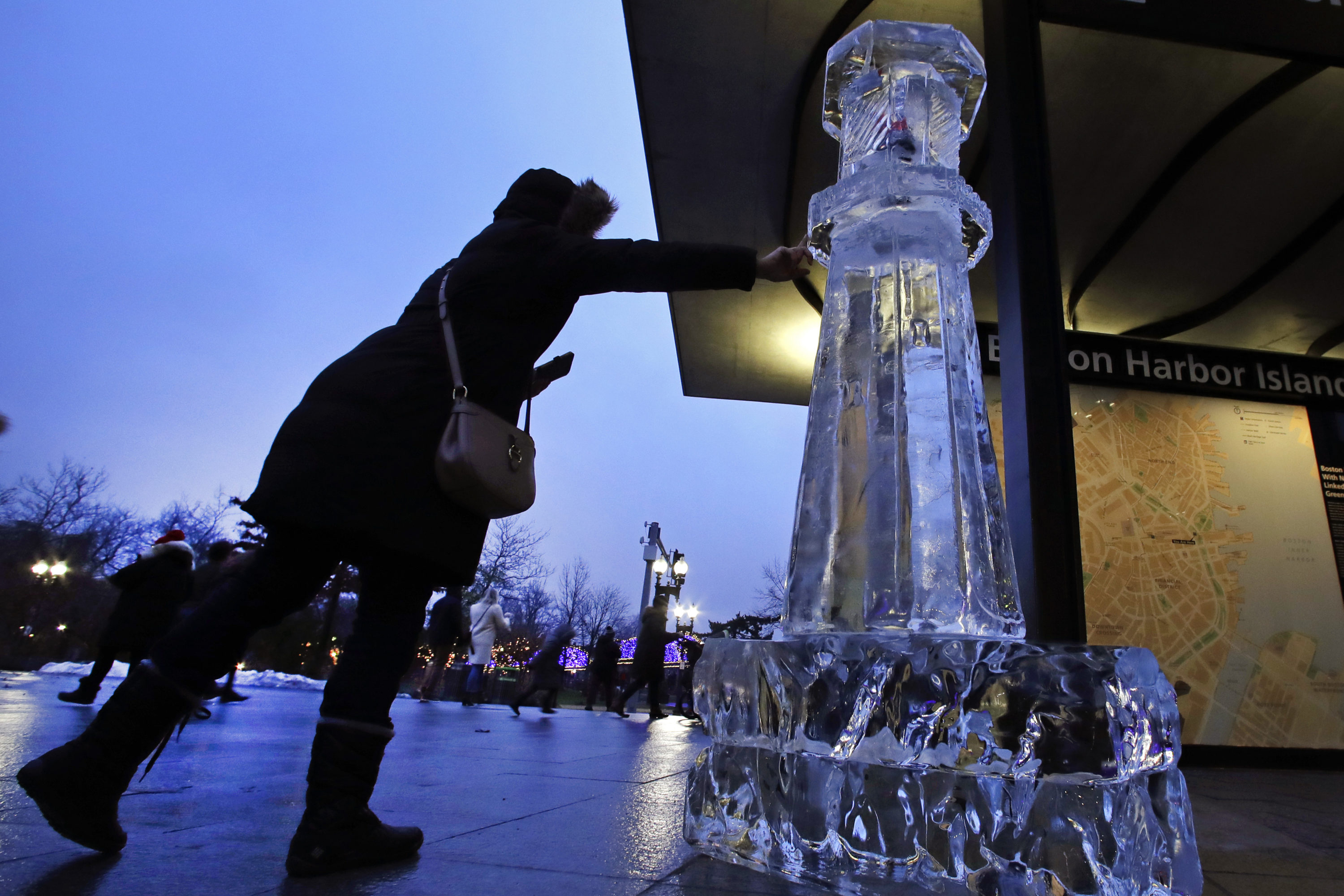 A woman reaches to touch a lighthouse ice sculpture, Friday, Dec. 31, 2019, in Boston. Ice sculptures make a return to the Boston Harborwalk for the 2020 First Night celebration. (AP Photo/Elise Amendola)