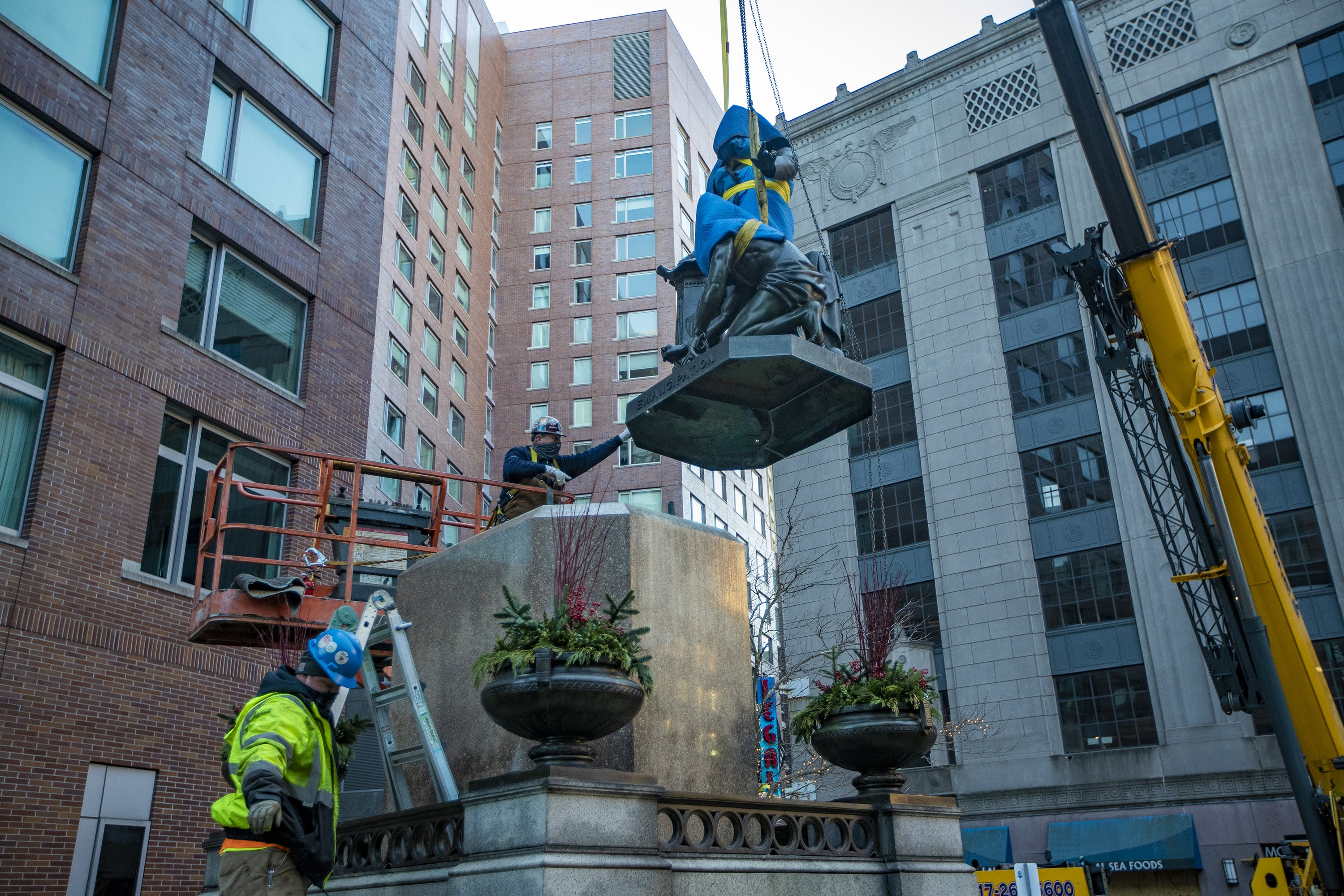 "Workers remove the ""Emancipation Group"" statue from its pedestal in Park Square. (Jesse Costa/WBUR)"