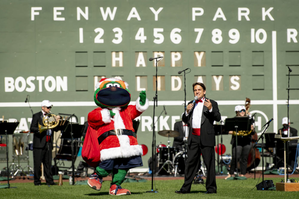 "Red Sox mascot Wally the Green Monster makes a cameo appearance for ""Must Be Santa"" while Lockhart and the orchestra members sing along. (Courtesy Maddie Malhotra/Boston Red Sox)"