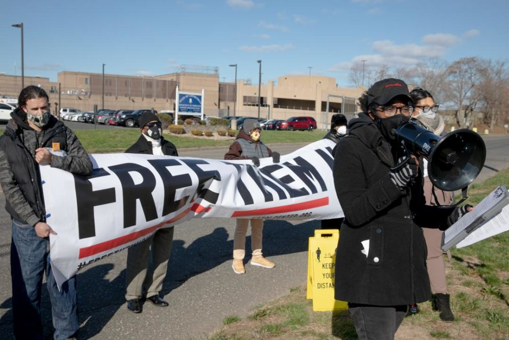 Kenyatta Thompson (right), a lead organizer of Katal Center, asks for the release of incarcerated individuals outside the Hartford Correctional Center. (Yehyun Kim/Connecticut Mirror)