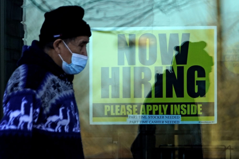 A shopper wears a face mask and he walks past a store displaying a hiring sign in Wheeling, Ill., Nov. 28, 2020. (Nam Y. Huh/AP)