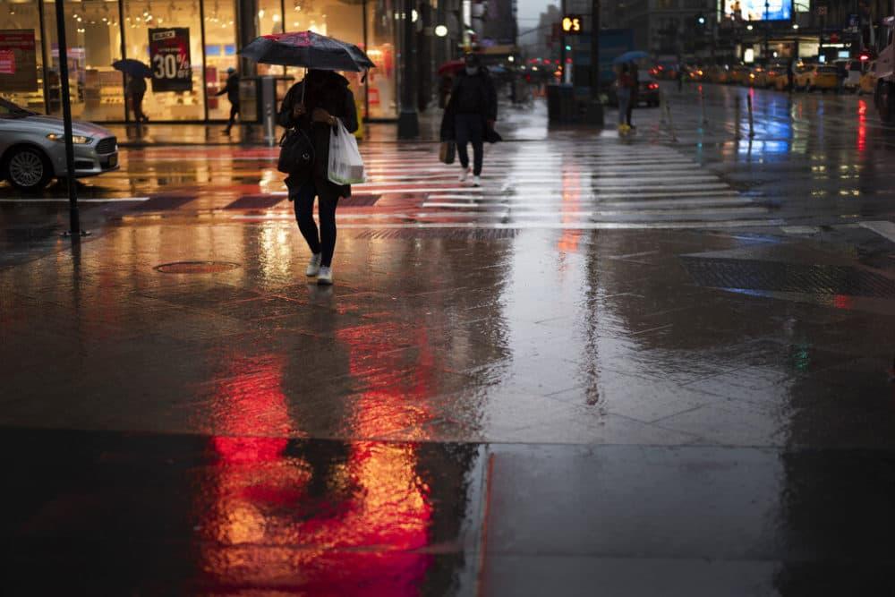 A shopper walks in a rainstorm, Nov. 30, 2020 in New York. (Mark Lennihan/AP)