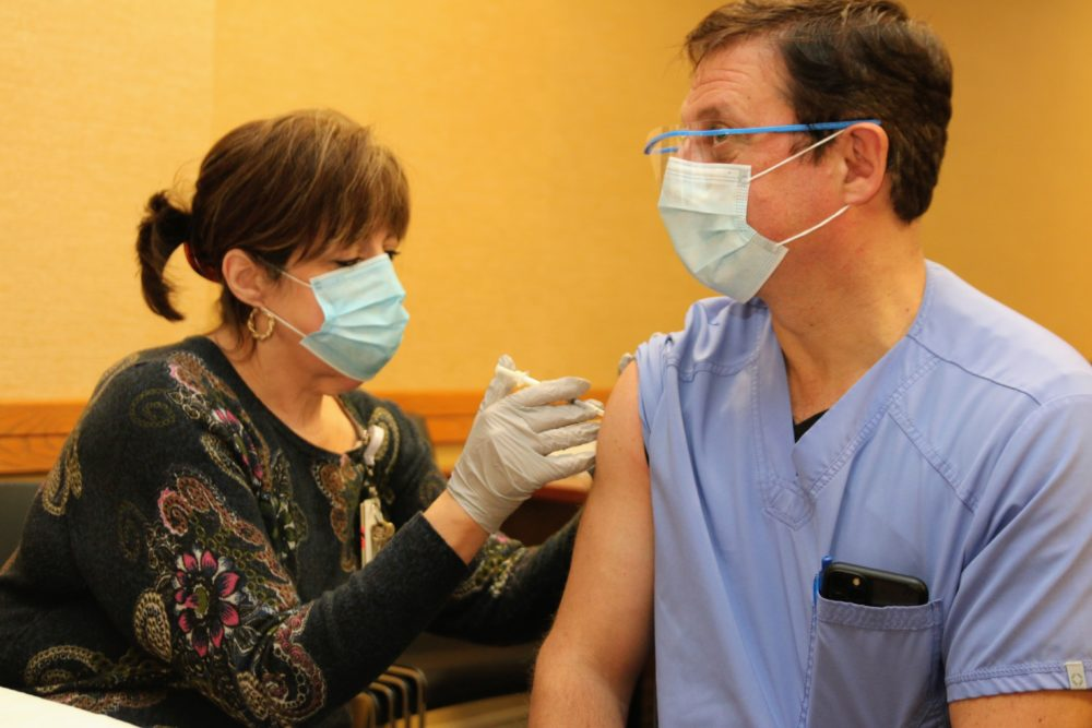 Dr. Dani Hackner, pulmonologist and chief clinical officer for Southcoast Health System, gets his first dose of the Pfizer-developed coronavirus vaccine on Tuesday. (Courtesy Southcoast Health System)