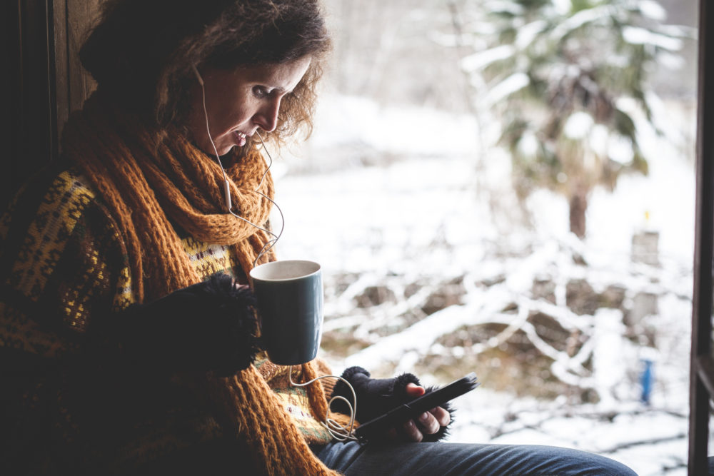 A woman listening to music as snow falls. (Getty Images)
