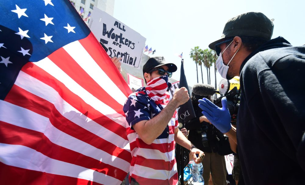 A protestor (L) argues with a counter-protestor (R) in front of the Los Angeles City Hall on May 1, 2020, to demand the end to the state's shutdown due to the coronavirus pandemic. (FREDERIC J. BROWN/AFP via Getty Images)
