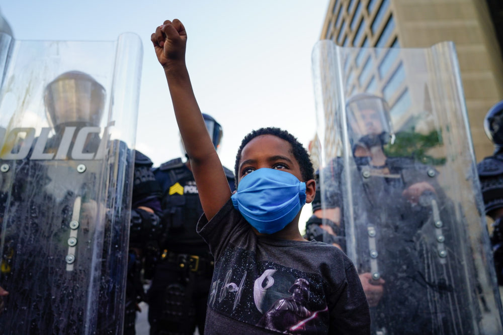 A young boy raises his fist for a photo by a family friend during a demonstration on May 31, 2020 in Atlanta, Georgia. (Elijah Nouvelage/Getty Images)