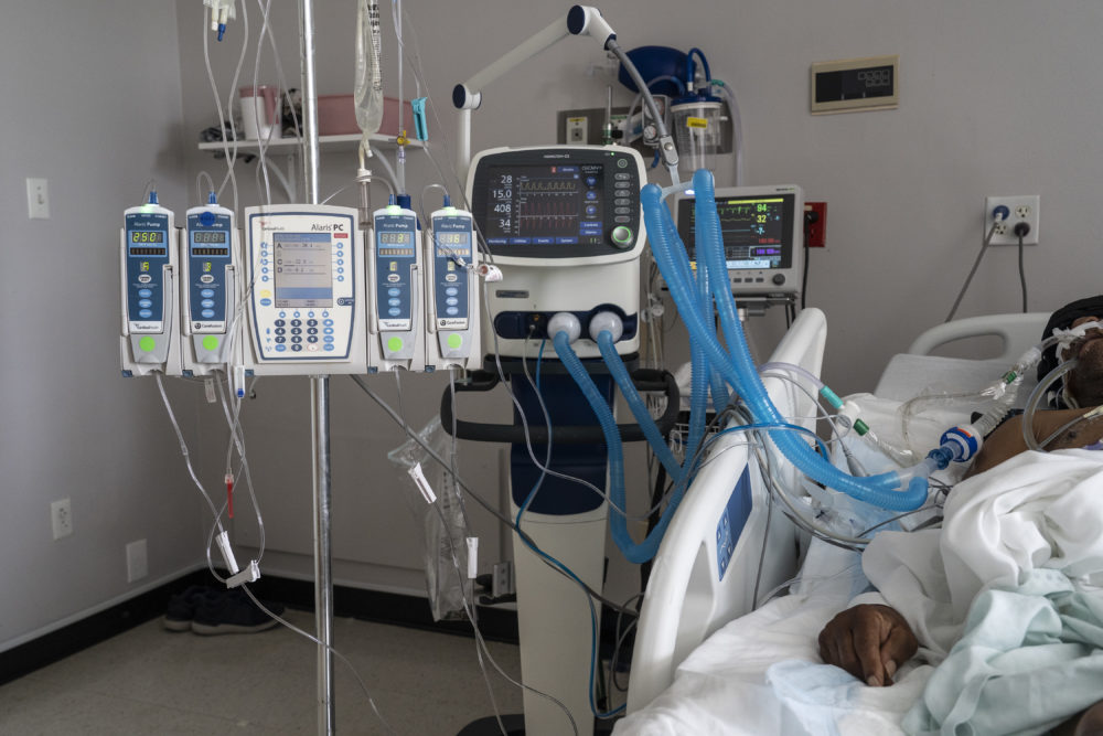 A patient is connected to a ventilator and other medical devices in a COVID-19 intensive care unit. (Go Nakamura/Getty Images)