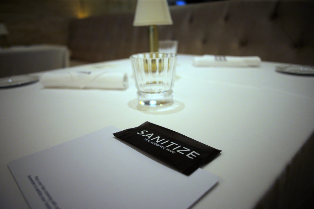 Tables in a restaurant with sanitizer, a mat for masks and wrapped utensils at The Encore Boston Harbor Casino in Everett on July 9, 2020. (Photo by Lane Turner/The Boston Globe via Getty Images)