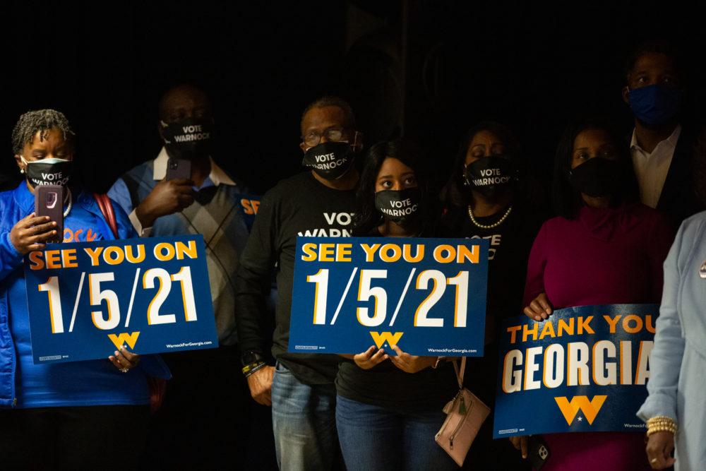 Family and supporters hold runoff signs as Democratic U.S. Senate candidate Rev. Raphael Warnock speaks during an Election Night event on November 3, 2020 in Atlanta, Georgia. (Jessica McGowan/Getty Images)