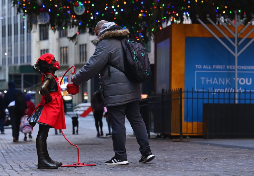 A man puts a donation into the red kettle next to the 'Fearless Girl' statue dressed in a Salvation Army uniform in front the of New York Stock Exchange on Dec. 10, 2020. The traditional Red Kettle donations started in Sept. 2020, some two months earlier than usual. The Salvation Army said the earlier start was due to the COVID-19 pandemic. (Angela Weiss/AFP/Getty Images)