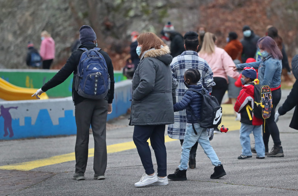 Teachers and students walk to the entrance at the Mattahunt Elementary School in Boston's Mattapan before the day's start on Dec. 14, 2020. (David L. Ryan/The Boston Globe via Getty Images)