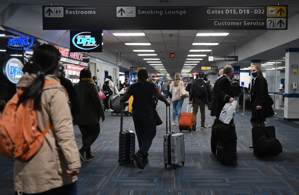 Passengers walk through a crowded terminal at Dulles International airport in Dulles, Virginia on Dec. 27, 2020 amid the coronavirus pandemic. (Photo by Andrew Caballero-Reynolds/AFP via Getty Images)