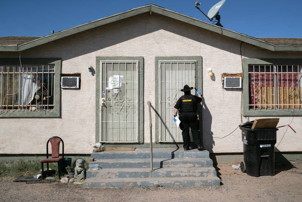 A Maricopa County constable knocks on a door before posting an eviction order on Oct. 1, 2020 in Phoenix, Arizona. (John Moore/Getty Images)