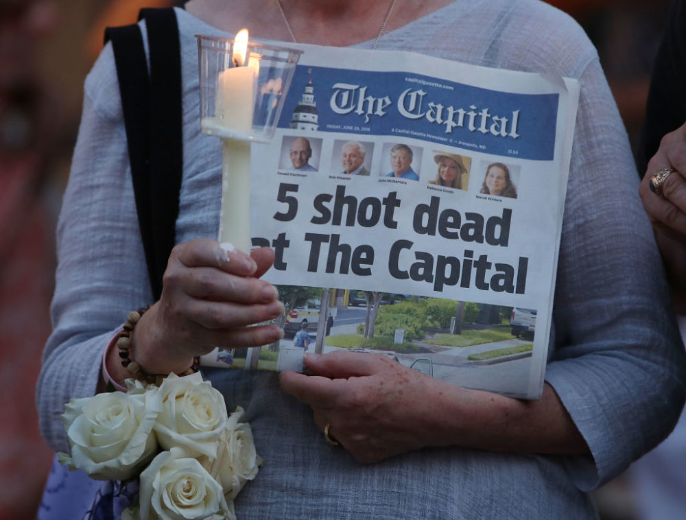 A women holds an edition of the Capital Gazette newspaper during a candlelight vigil to honor the five people who were shot and killed on June 29, 2018 in Annapolis, Maryland. (Mark Wilson/Getty Images)