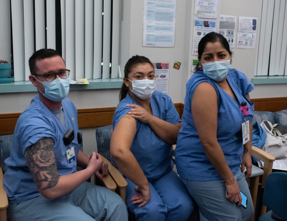 Staffers at the Cambridge Health Alliance clinic for COVID-19 patients in Somerville -- RN Erik Westhaver and Medical Assistants Nancy Morales and Carla Ayala -- show off their newly vaccinated arms. (Courtesy Dr. Anna Rabkina, Cambridge Health Alliance)
