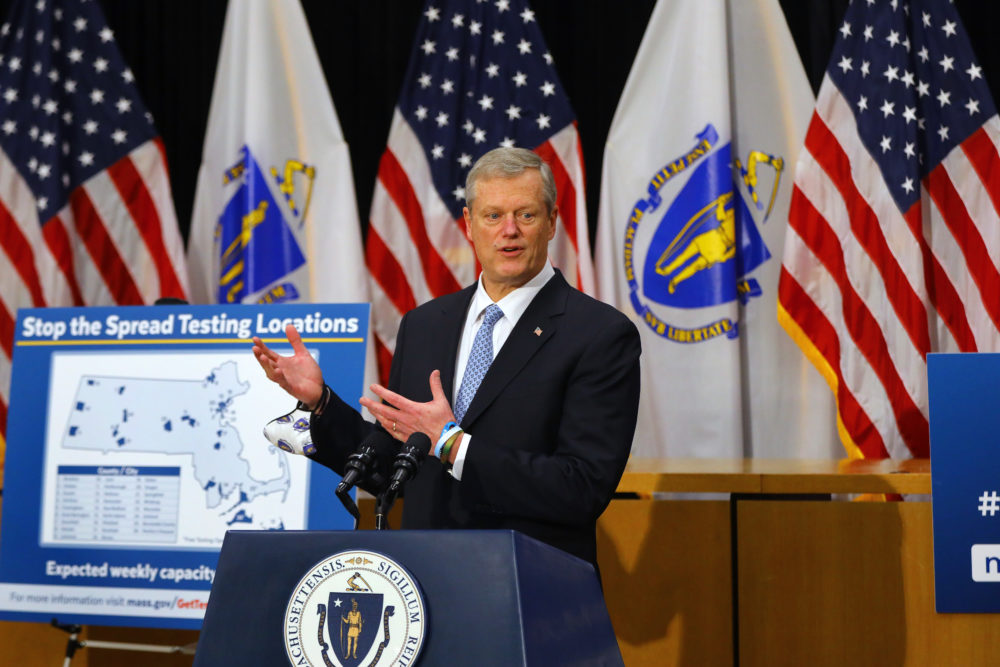 "Gov. Charlie Baker stands next to a sign reading ""Stop the Spread Testing Locations"" as he speaks during a press conference in the Gardner Auditorium in the State House in Boston on Dec. 7. (Pat Greenhouse/The Boston Globe via Getty Images)"