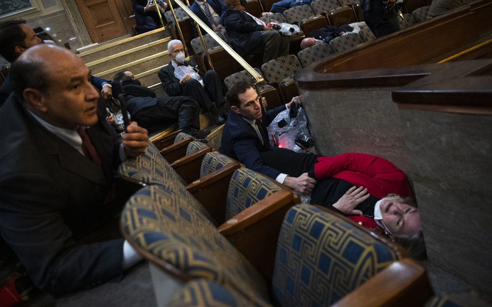 Rep. Jason Crow (D-Colo.), comforts Rep. Susan Wild, (D-Penn.), while taking cover as protesters disrupt the joint session of Congress to certify the Electoral College vote on Jan. 6, 2021. (Tom Williams/CQ-Roll Call, Inc via Getty Images)