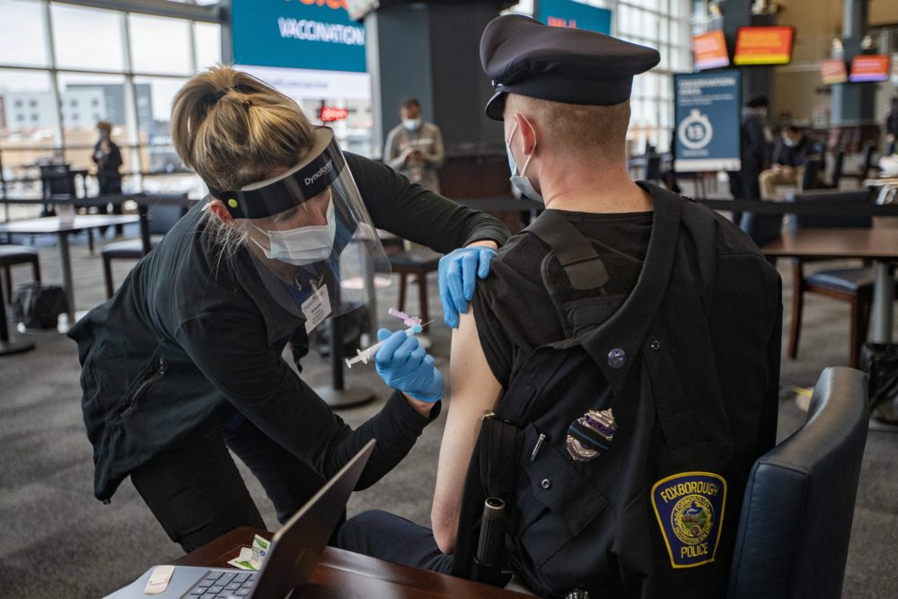 Registered nurse Samantha Schuko prepares to vaccinate Foxborough Police Officer Brendan Fayles with the Moderna COVID-19 vaccine at the Gillette Stadium COVID-19 Vaccination Site. (Jesse Costa/WBUR)