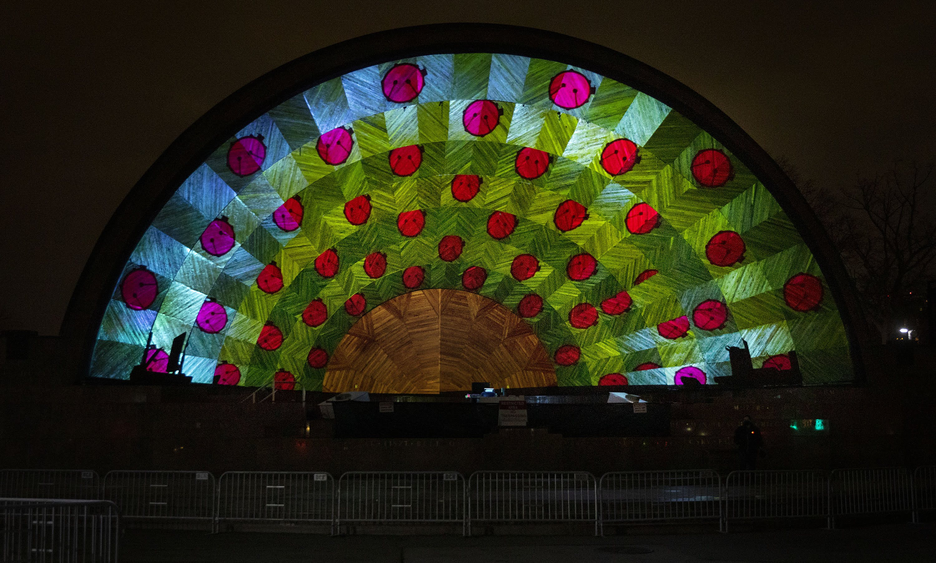"The Hatch Shell, lit up with patterns and drums, as the artist team sets up ""Hatched: Breaking through the Silence."" (Robin Lubbock/WBUR)"