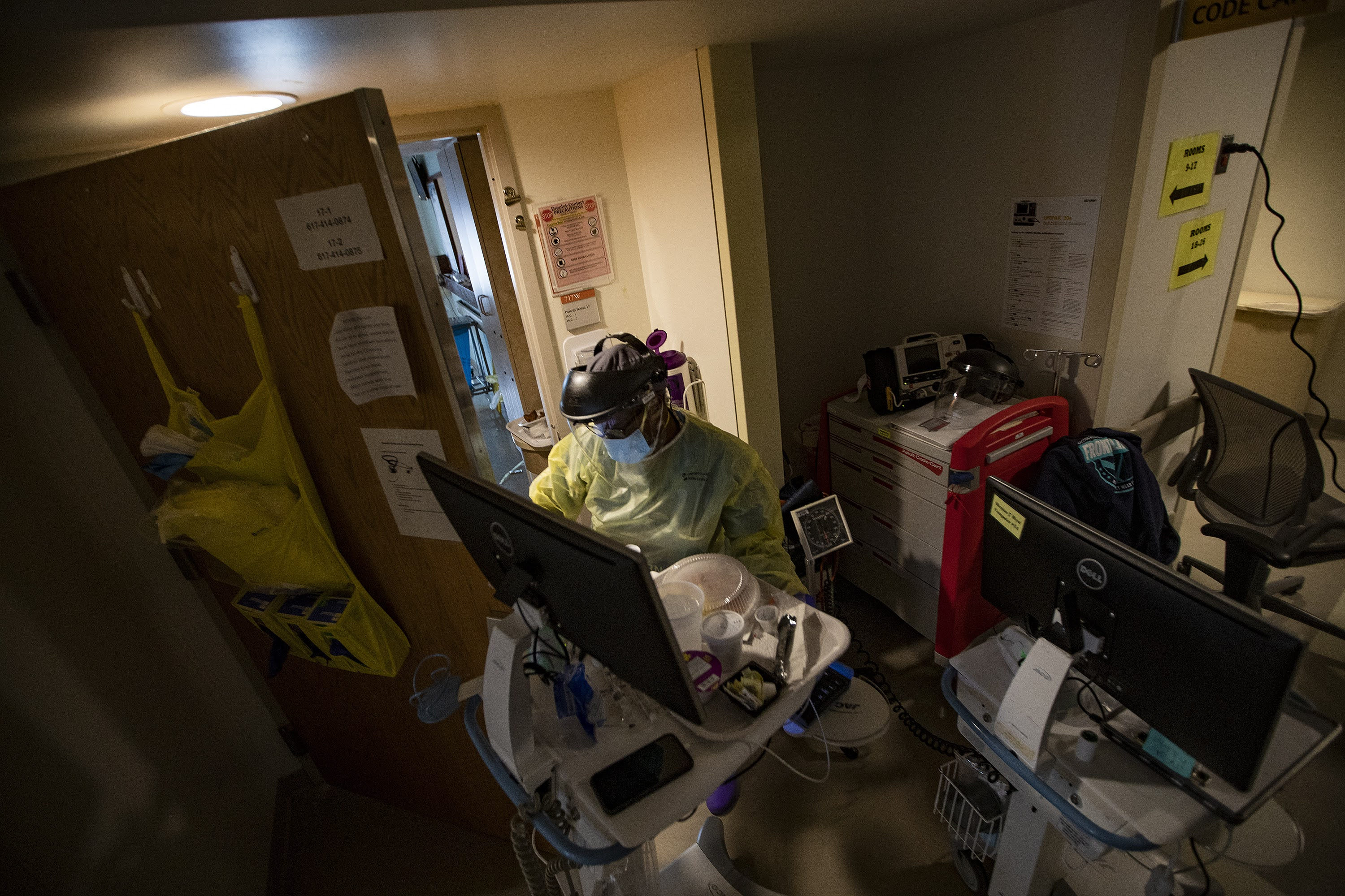 Boston Medical Center registered nurse Ellen Stephenson prepares to enter a room of a COVID-19 patient with supplies. (Jesse Costa/WBUR)